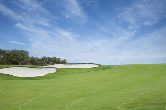 Golf Fairway with Sand Traps and Blue Sky with Clouds