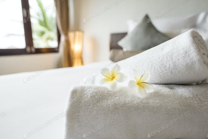 Rolled up clean towels on a bed