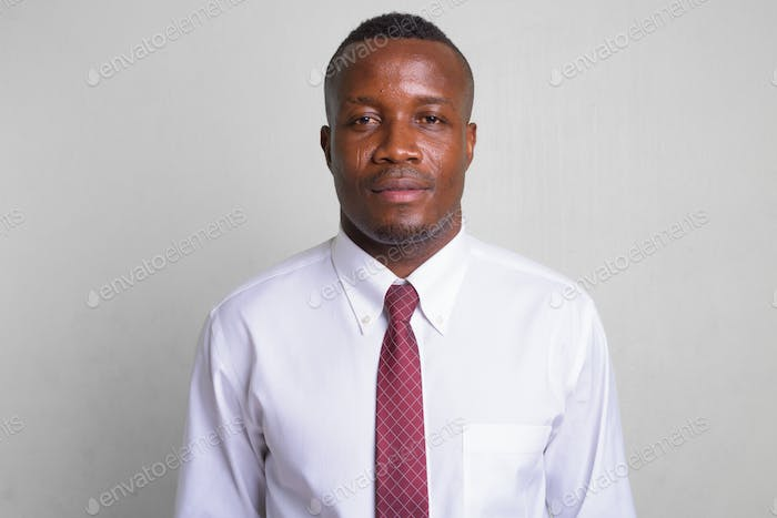 Young African businessman wearing red tie against white background