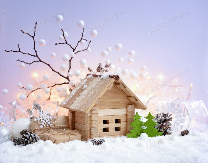 Christmas decorative landscape with toy house in snow, gifts and