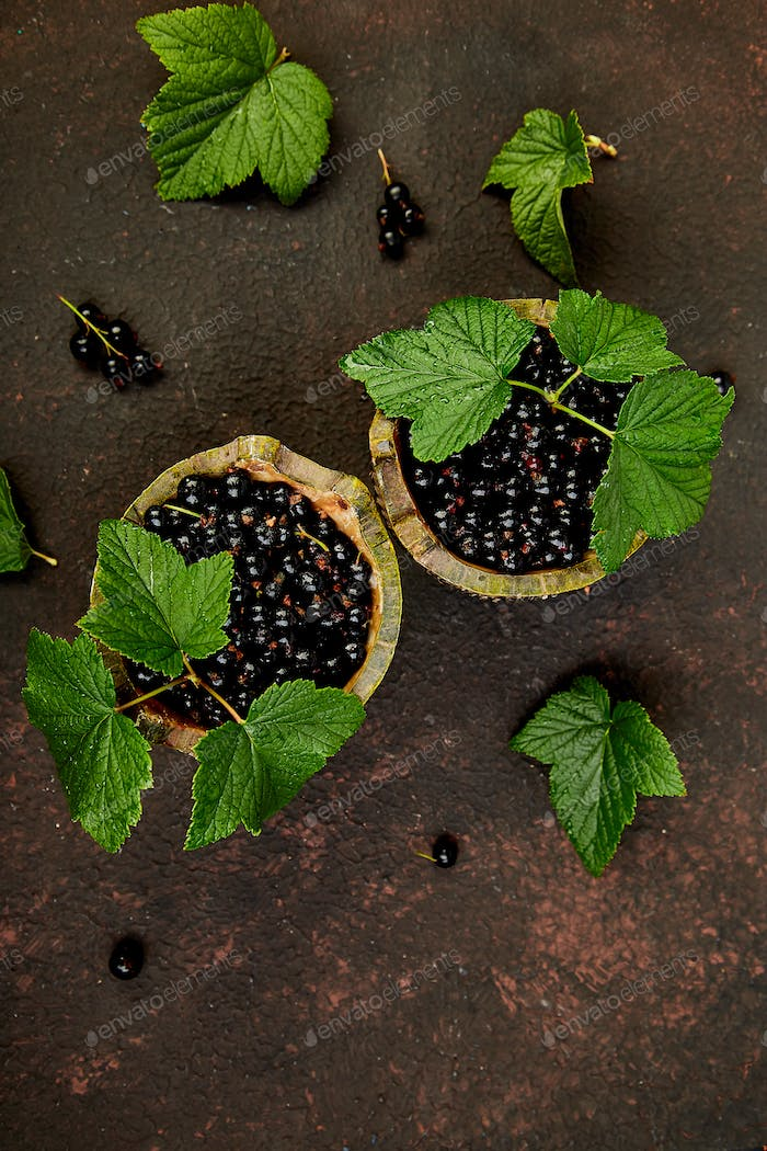 Blackcurrant berries with leaves, black currant in green bowls.