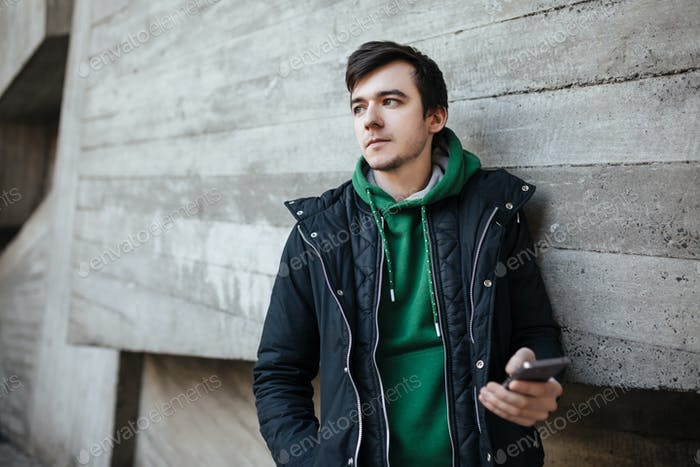 Young man with dark hair in black jacket standing outside with mobile phone in hand