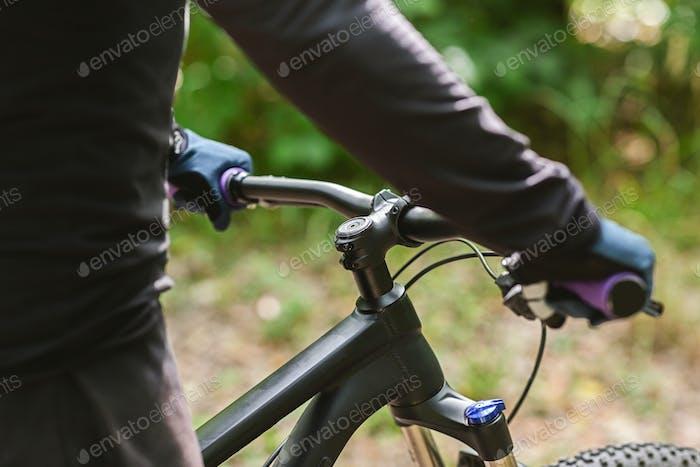Человек держит велосипед руль, Велоспорт в лесу