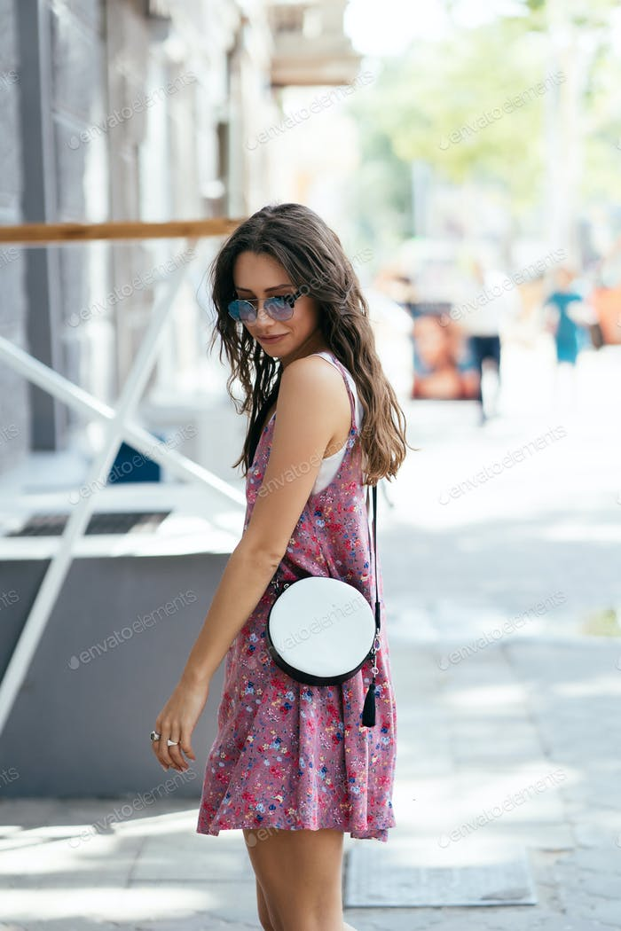 Girl posing for the camera with a female bag