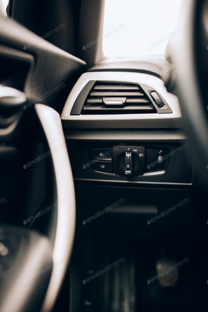CLose up interior of modern car, details of light switch and ventilation holes