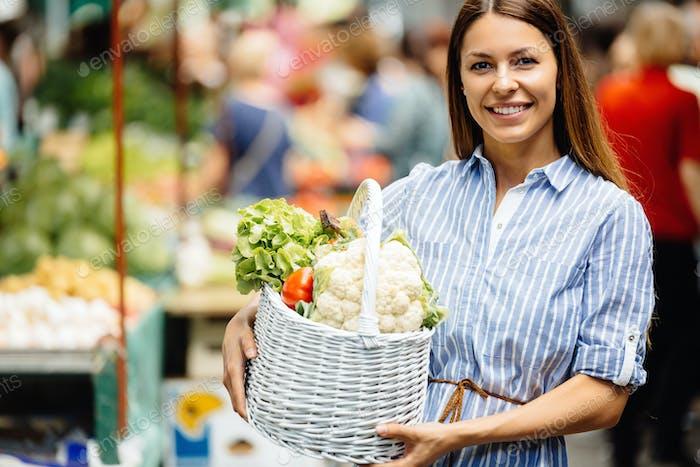 Portrait of beautiful woman holding shopping basket