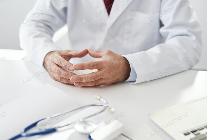 Close up of a doctor sitting at a desk