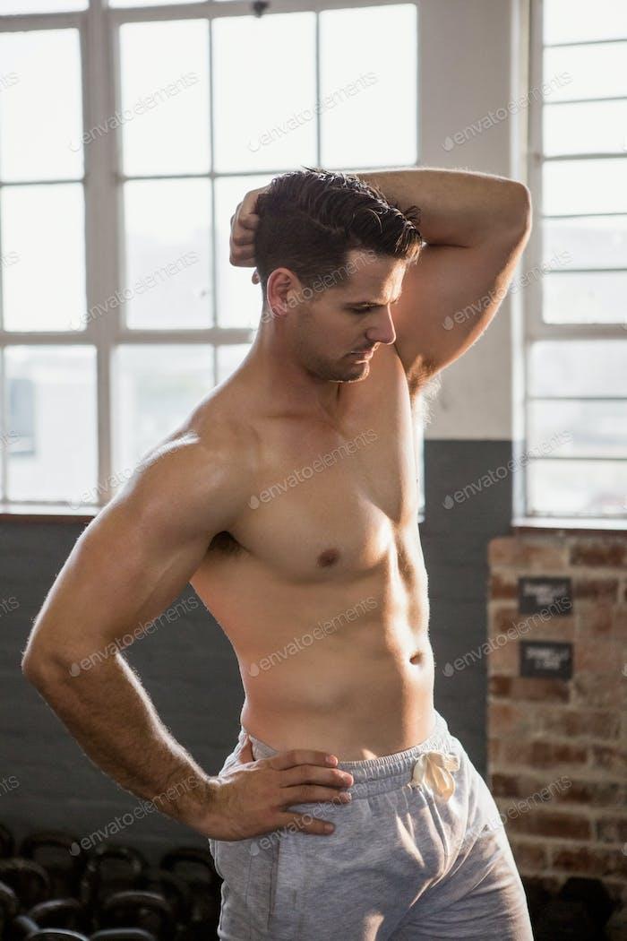 Shirtless muscular man posing at the gym