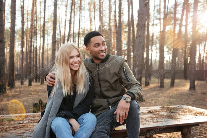 Happy loving couple sitting outdoors in the forest.