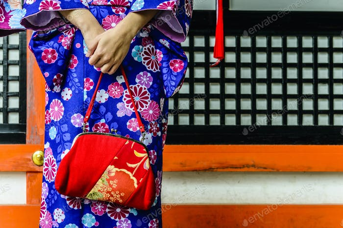 Close up of woman in kimono holding purse