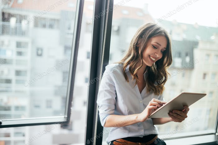Attractive businesswoman using a digital tablet while standing in front of windows