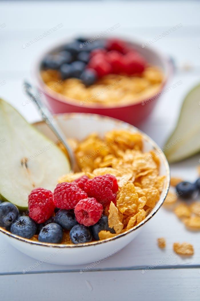Goldene Cornflakes mit frischen Früchten von Himbeeren, Heidelbeeren und Birne in Keramikschale