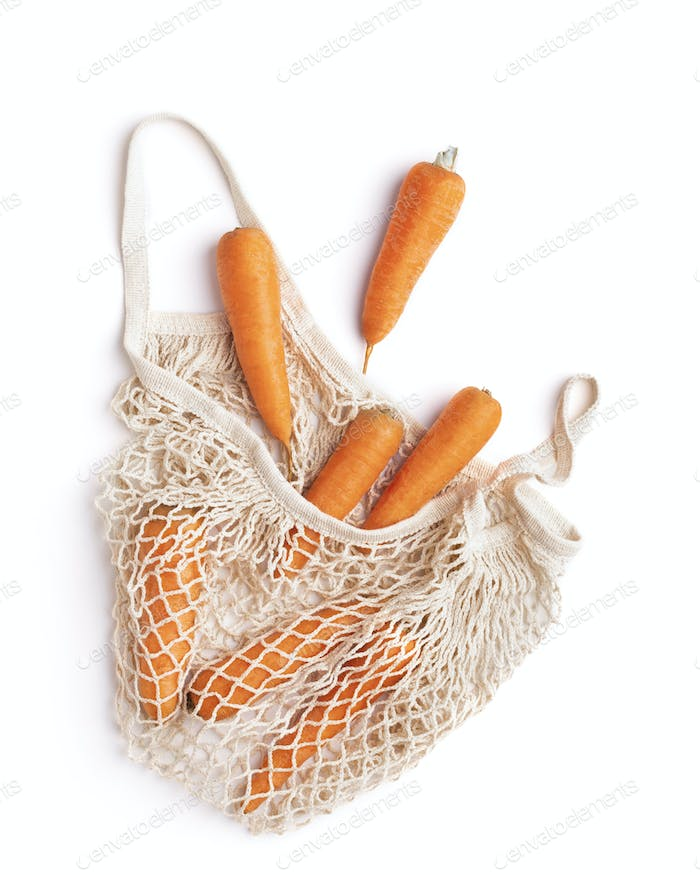 Clean fresh carrots inside mesh eco shopper isolated on white