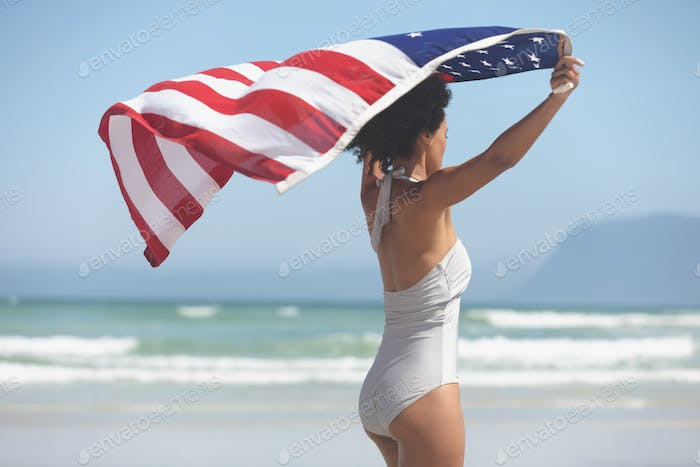 Woman holding american flag at beach on a sunny day. American flag waving on beach