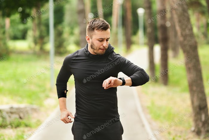 Guy Running Checking Activity Tracker On Wrist Watch