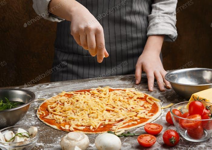 Preparing pizza. Woman adding cheese to pizza