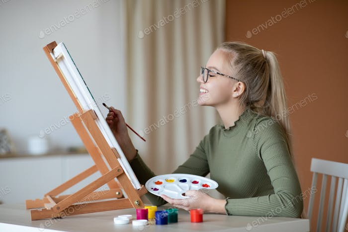 Talented girl holding palette and brush, painting