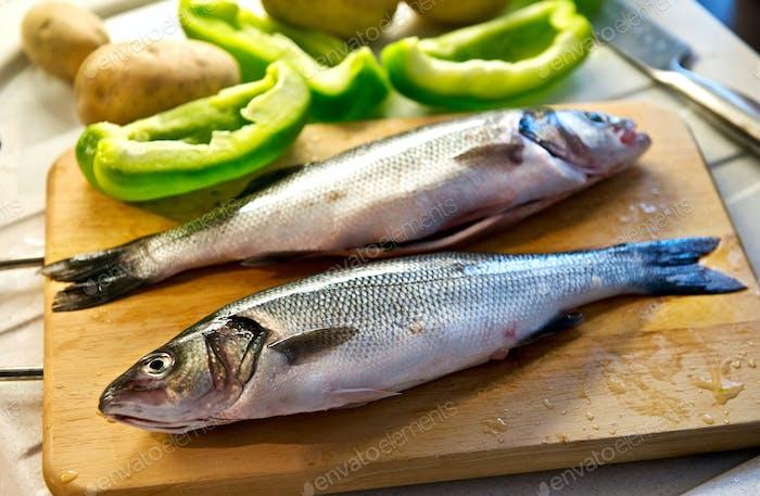 Whole fresh caught sea bass on a chopping board