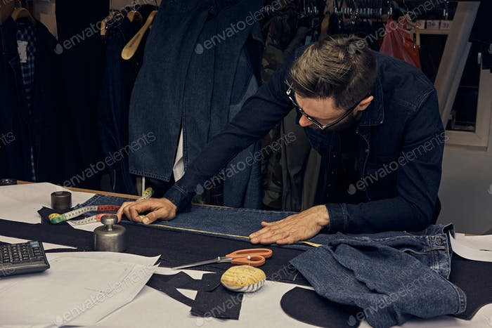 Handsome bearded tailor working with cloth samples at sewing workshop.