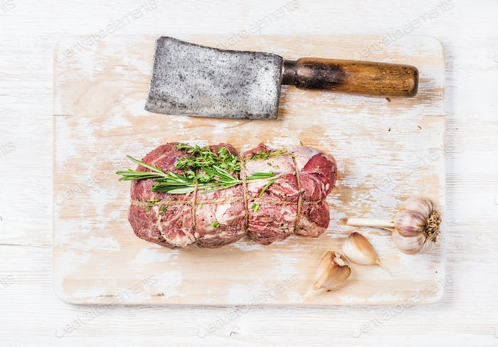 Raw roastbeef meat cut with rosemary, thyme and garlic