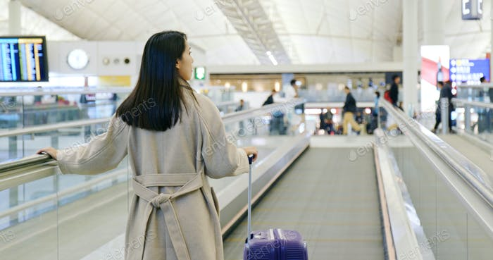 Woman walking in the airport with her luggage