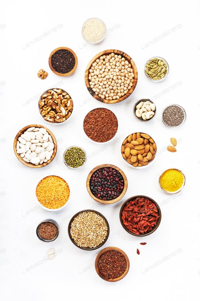 Various superfoods, legumes, cereals, nuts, seeds in bowls