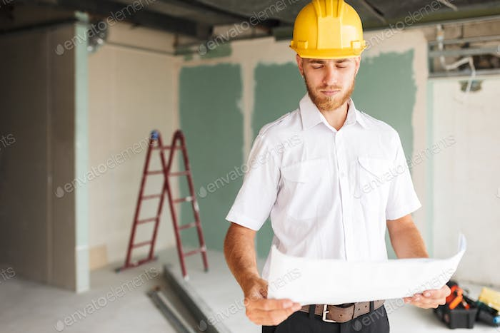 Young architect in white shirt and yellow hardhat thoughtfully l