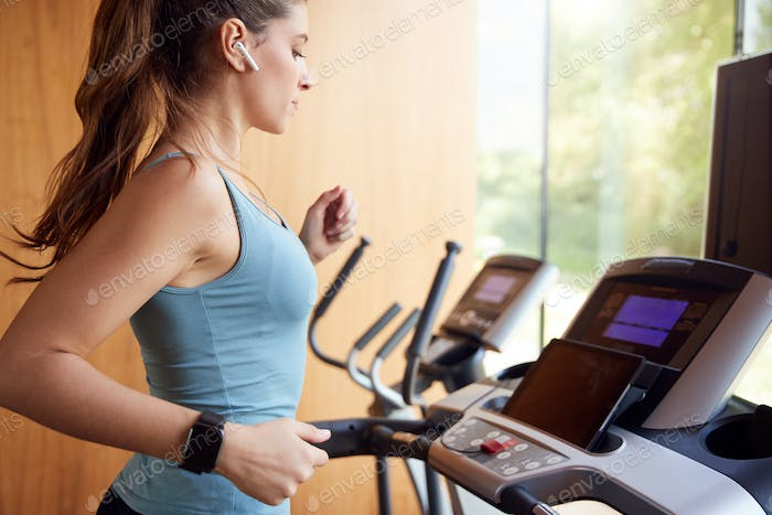 Woman Exercising On Treadmill At Home Wearing Wireless Earphones Checking Smart Watch