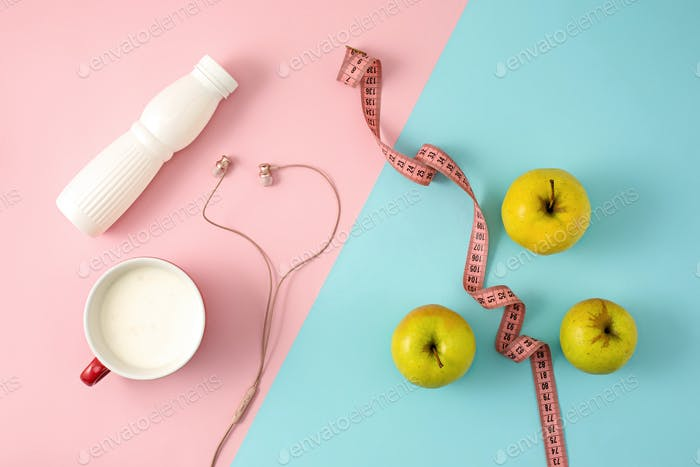 The green apple and bottle of yogurt with measure tape