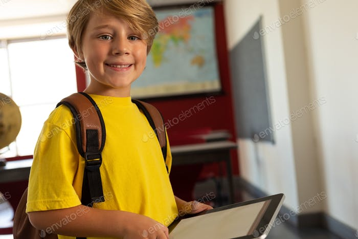 Happy boy with school bag and digital tablet looking at camera in a classroom at elementary school