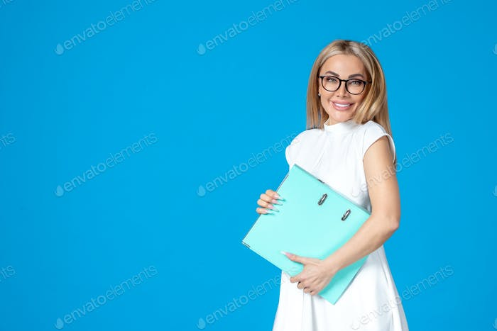 front view female worker in white dress holding blue files on blue background authority success