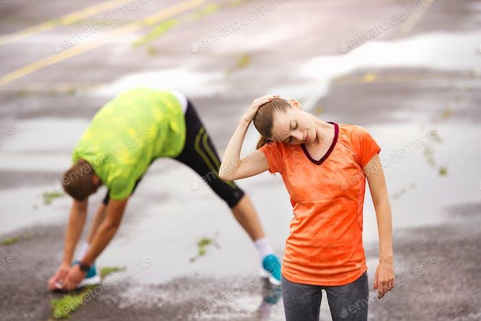 Paar Stretching bei Regenwetter