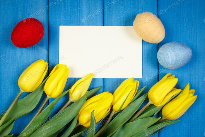 Tulips and Easter eggs wrapped woolen string, copy space for text on sheet of paper