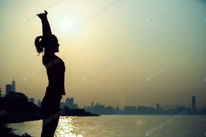 Silhouette of woman stretching arms during sunrise
