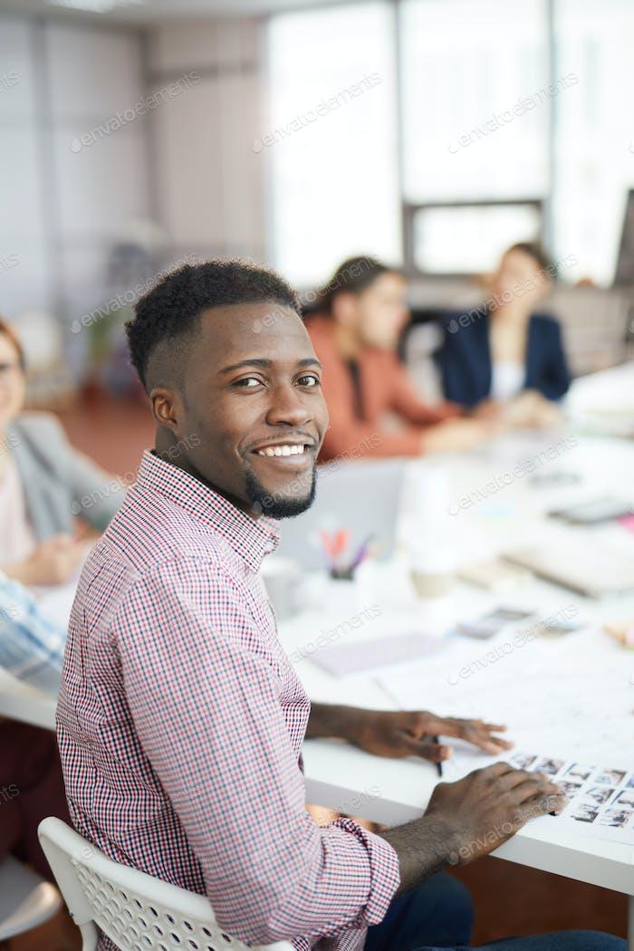 Улыбающийся афро-американский человек позирует в производственном Агентство
