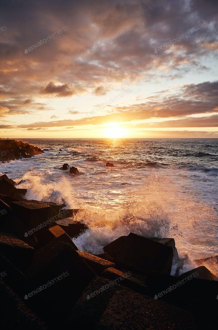 Scenic sunset with waves crashing on rocks.