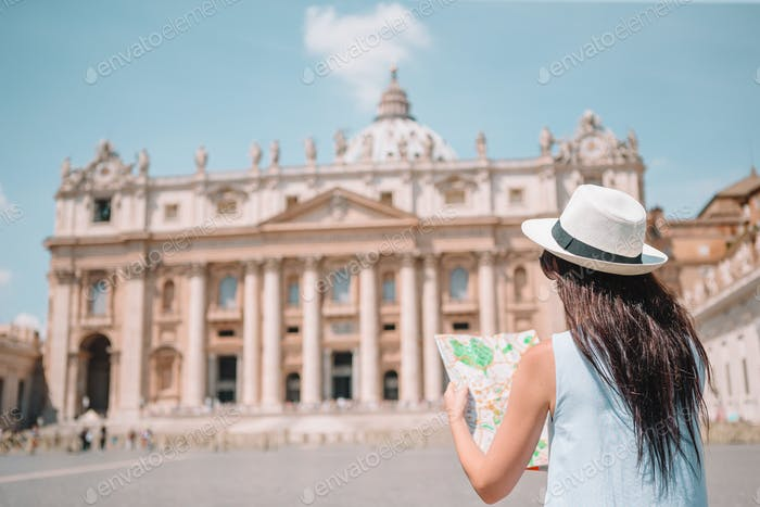 Happy young woman with city map in Vatican city and St. Peter's Basilica church, Rome, Italy