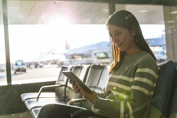 Frau mit Tablet-PC in der Abflughalle des Flughafens