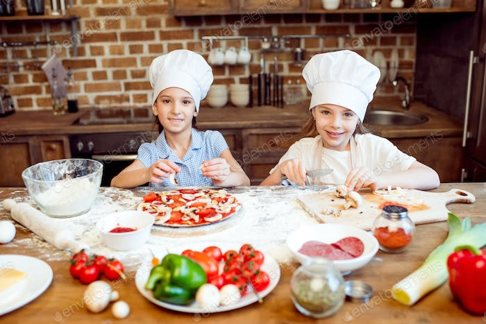 kids in chef hats making pizza together