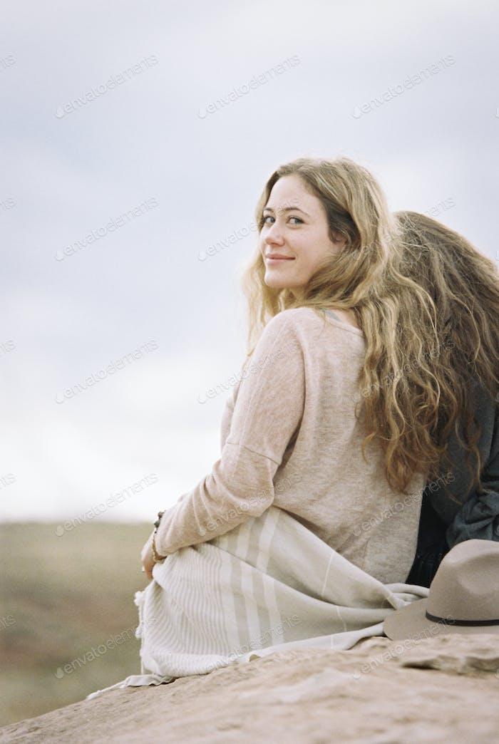 Two women sitting side by side on a rock