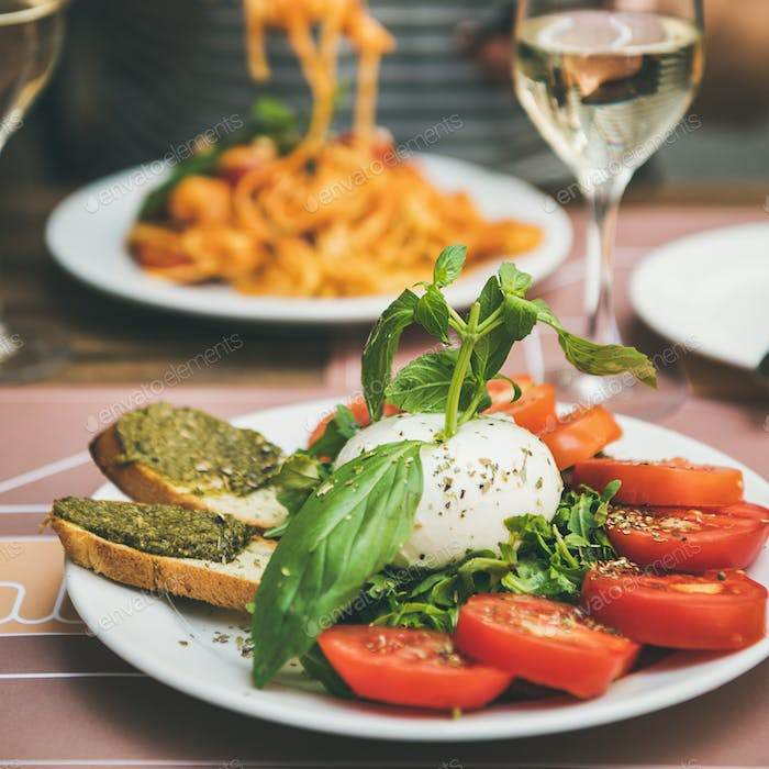 Italian dinner at bistrot with caprese and pasta, square crop