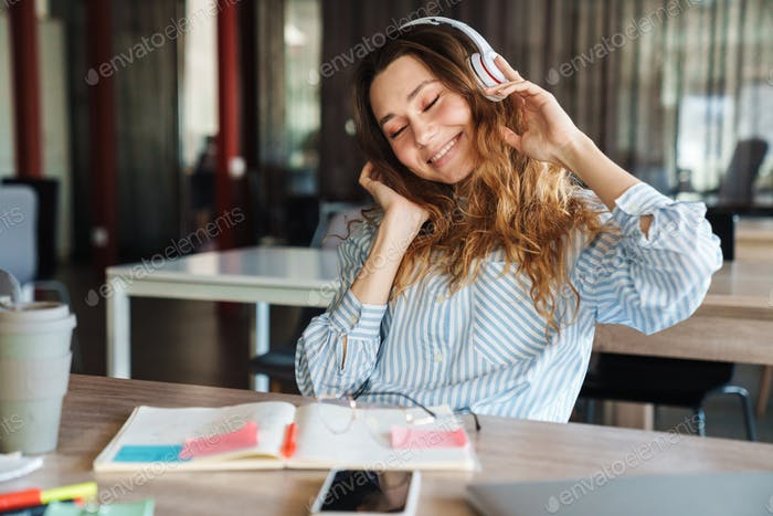 Image of woman listening music with wireless headphones while studying