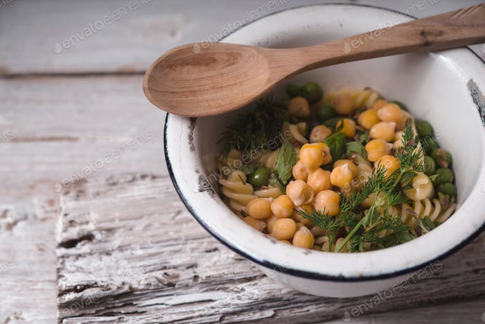 Salad with fusilli, chickpeas and peas in a white bowl