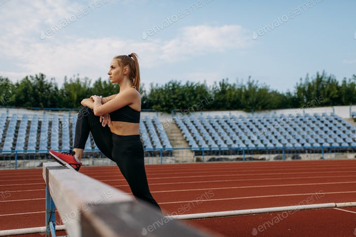 Female runner, stretching workout on stadium