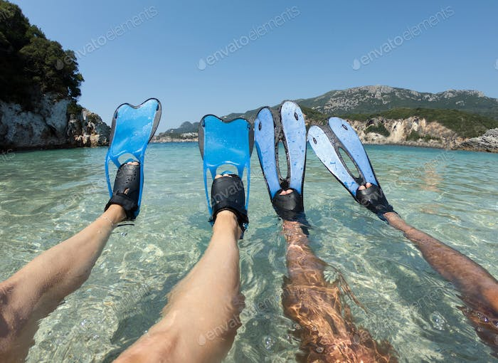 Snorkeler couple relaxing on the beach. Tanned legs in blue fins, flippers