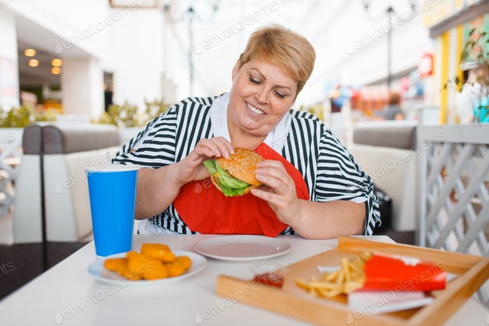Fat woman eating fastfood in mall food court