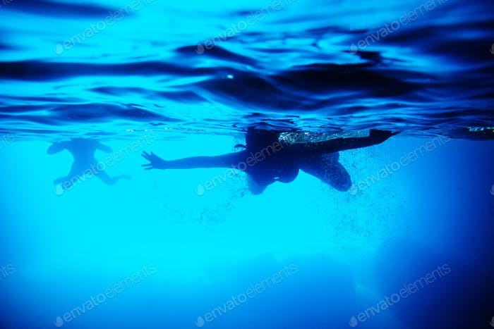 silhouette of people swim underwater