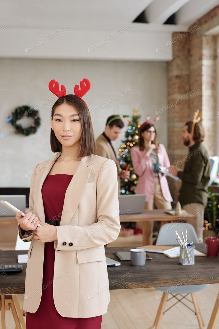Young pretty Asian businesswoman in smart casualwear and xmas headwear