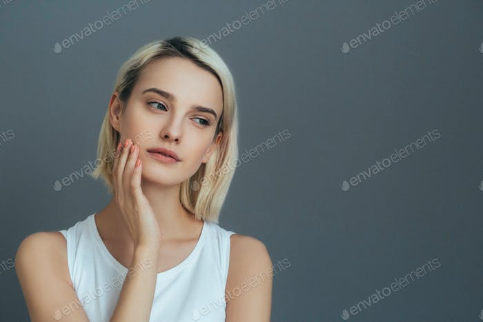 Beautiful woman natural casual female short blond hair portrait beauty model over gray background