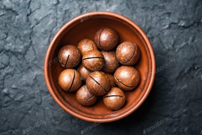Getrocknete Bio-Macadamia-Nüsse in orangefarbener Keramikschale